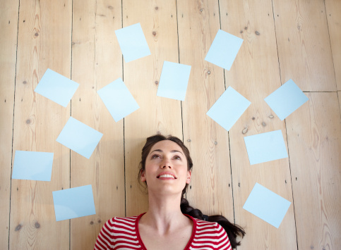 Woman surrounded by blank sheets of paper